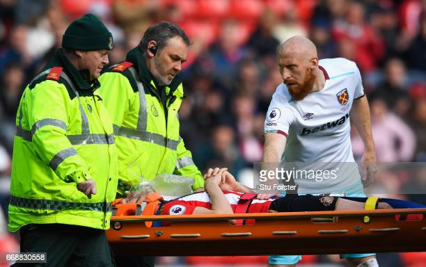 James Collins of West Ham United stands over Billy Jones of Sunderland as he is stretchered off through injury during the Premier League match...