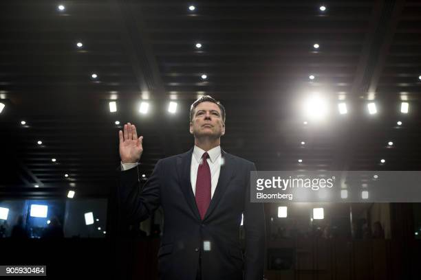 James Comey former director of the Federal Bureau of Investigation swears in to a Senate Intelligence Committee hearing in Washington DC US on...