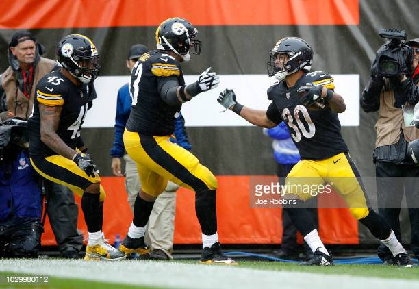 James Conner celebrates his touchdown with Maurkice Pouncey and Roosevelt Nix-Jones of the Pittsburgh Steelers during the third quarter against the...