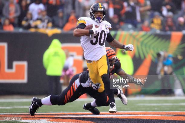 James Conner of the Pittsburgh Steelers breaks a tackle by Geno Atkins of the Cincinnati Bengals during the third quarter at Paul Brown Stadium on...