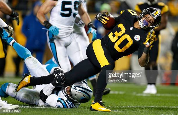 James Conner of the Pittsburgh Steelers carries the ball against Eric Reid of the Carolina Panthers during the first half in the game at Heinz Field...