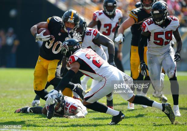 James Conner of the Pittsburgh Steelers carries the ball against Isaiah Oliver of the Atlanta Falcons in the second half during the game at Heinz...
