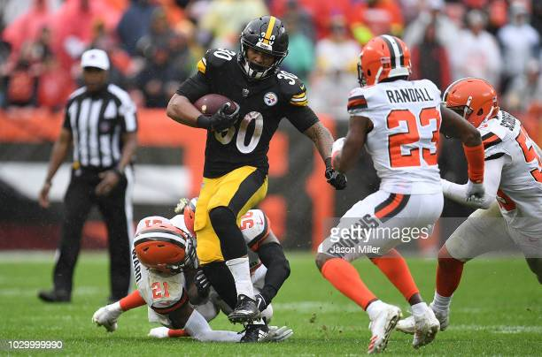 James Conner of the Pittsburgh Steelers carries the ball between the defense of Denzel Ward and Damarious Randall of the Cleveland Browns during the...