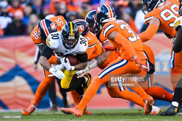 James Conner of the Pittsburgh Steelers is tackled by Derek Wolfe of the Denver Broncos and company during the second quarter on Sunday November 25...