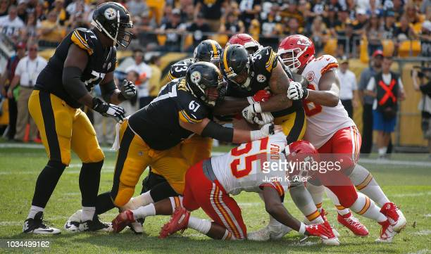 James Conner of the Pittsburgh Steelers is wrapped up for a tackle by Dee Ford of the Kansas City Chiefs in the second half during the game at Heinz...