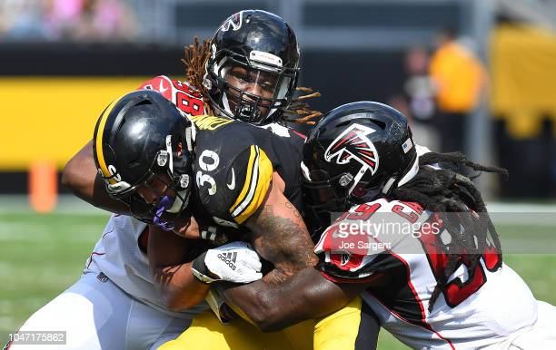 James Conner of the Pittsburgh Steelers is wrapped up for a tackle by Takkarist McKinley and De'Vondre Campbell of the Atlanta Falcons in the first...