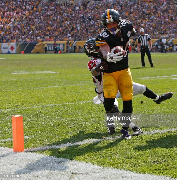 James Conner of the Pittsburgh Steelers runs into the end zone past Duke Riley of the Atlanta Falcons for a 2 yard touchdown in the second half...