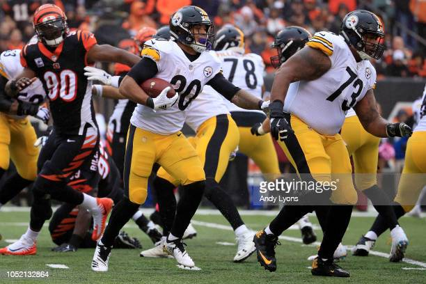 James Conner of the Pittsburgh Steelers runs the ball as Ramon Foster blocks during the second quarter of the game against the Cincinnati Bengals at...