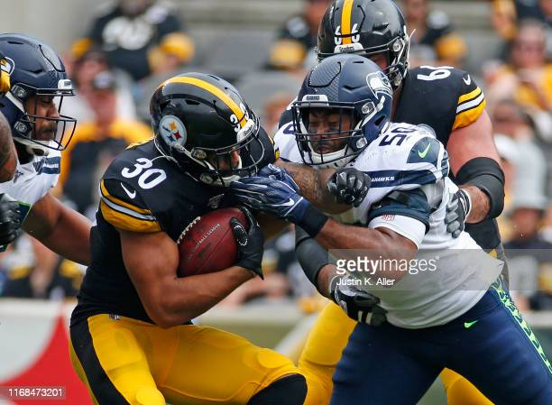 James Conner of the Pittsburgh Steelers rushes against K.J. Wright of the Seattle Seahawks on September 15, 2019 at Heinz Field in Pittsburgh,...