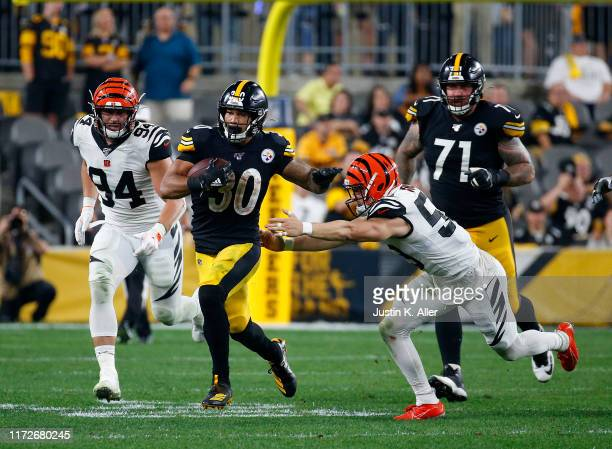 James Conner of the Pittsburgh Steelers rushes in the second half against Sam Hubbard and Nick Vigil of the Cincinnati Bengals on September 30, 2019...