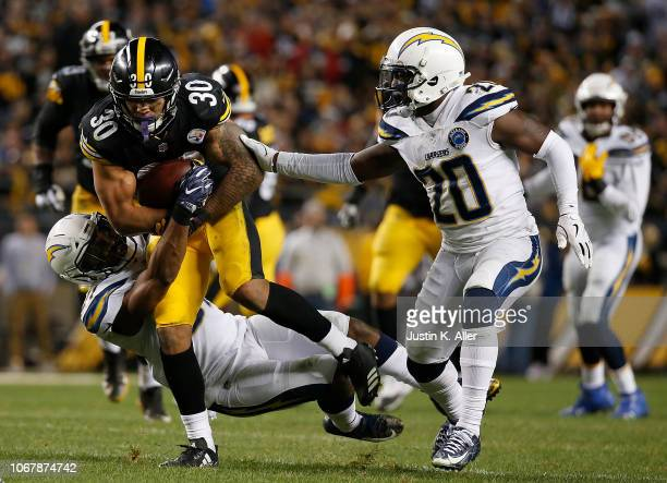 James Conner of the Pittsburgh Steelers rushes the ball against Desmond King of the Los Angeles Chargers in the second half during the game at Heinz...