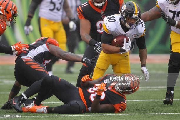 James Conner of the Pittsburgh Steelers slips past Vontaze Burfict and Shawn Williams of the Cincinnati Bengals during the third quarter at Paul...