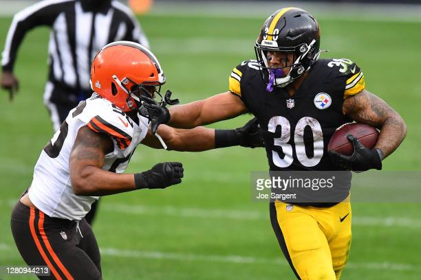 James Conner of the Pittsburgh Steelers stiff arms Malcolm Smith of the Cleveland Browns during their NFL game at Heinz Field on October 18, 2020 in...