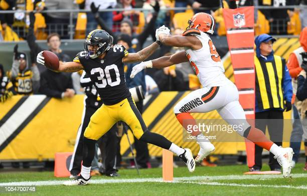 James Conner of the Pittsburgh Steelers stretches past Myles Garrett of the Cleveland Browns for a 12 yard touchdown during the third quarter in the...