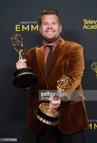 James Corden poses in the press room with the awards for outstanding short form variety series and outstanding variety special for 'Carpool Karaoke...