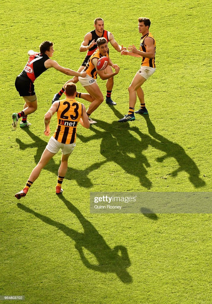 James Cousins of the Hawks handballs whilst being tackled by Zach Merrett of the Bombers during the round seven AFL match between the Essendon Bombers and the Hawthorn Hawks at Melbourne Cricket Ground on May 5, 2018 in Melbourne, Australia.