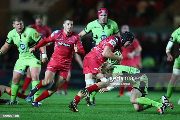 James Davies of Scarlets is hed up by Joel Hodgson of Northampton Saints during the LV=Cup match between Scarlets and Northampton Saints at Parc y...
