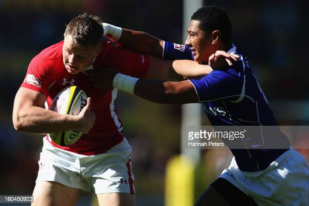 James Davies of Wales fends off Patrick Faapale of Samoa during the Pool C match between Wales and Samoa during the 2013 Wellington Sevens at Westpac...