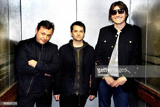 James Dean Bradfield, Sean Moore and Nicky Wire of Manic Street Preachers pose backstage after signing copies of their new album 'Rewind The Film' at...