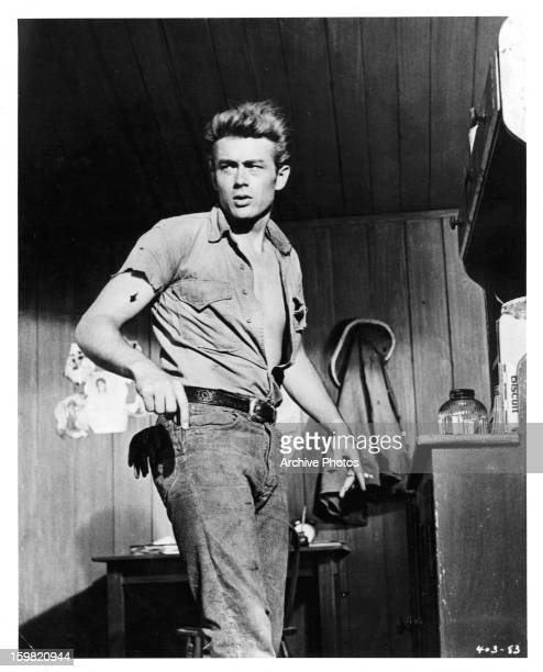 James Dean holding cigarette and looking to his right in a scene from the film 'Giant' 1956