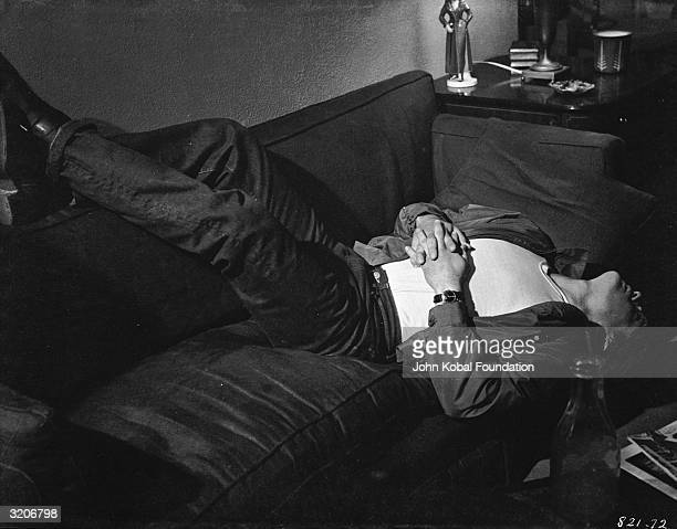 James Dean lying on a sofa during a scene from Nicholas Ray's film 'Rebel Without A Cause'