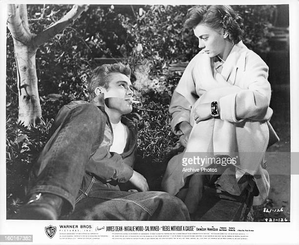 James Dean reclined on the ground with a cigarette in his mouth looks up at Natalie Wood in a scene from the film 'Rebel Without A Cause' 1955