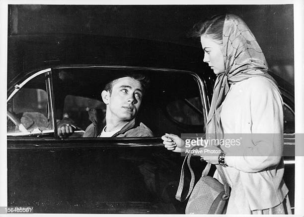 James Dean sits in his car as he talks to Natalie Wood in a scene from the film 'Rebel Without A Cause' 1955