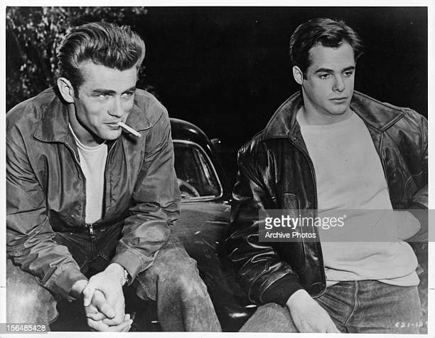 James Dean sits on a car and smokes with a friend in a scene from the film 'Rebel Without A Cause' 1955