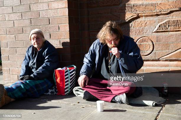 James Deane has a bad cough but he and friend Marla say they feel alright as they sit on the sidewalk on April 6 2020 in Seattle Washington Both of...