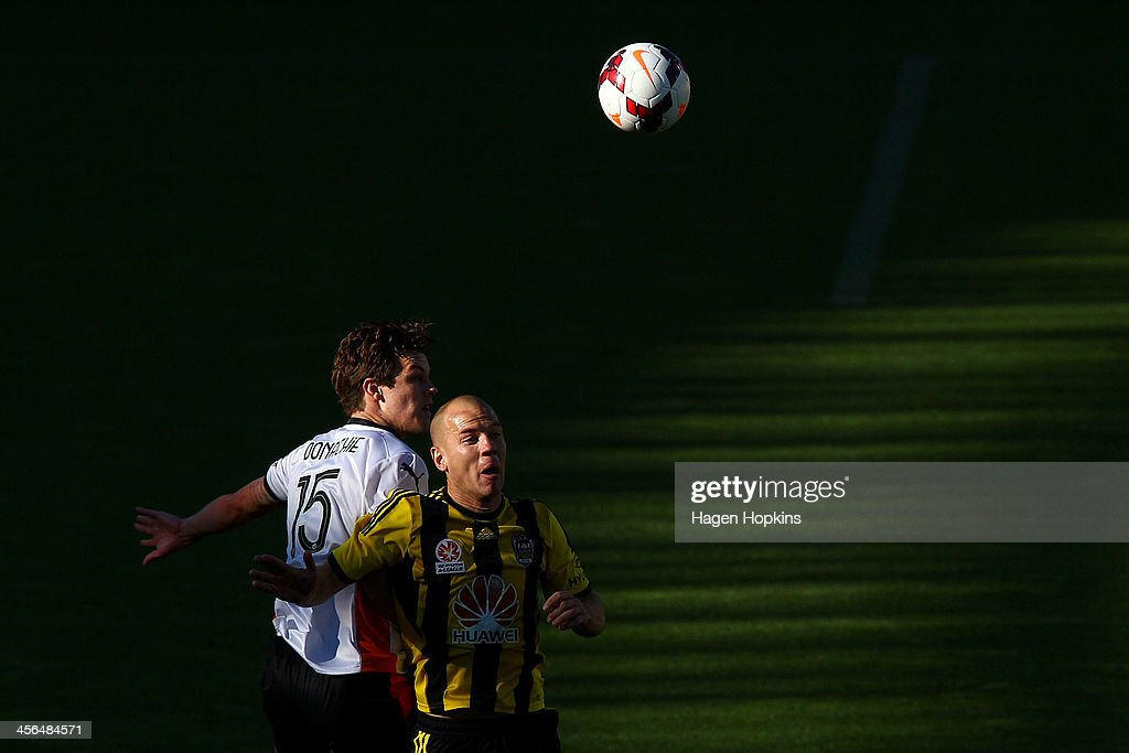 James Donachie of the Roar and Stein Huysegems of the Phoenix compete for a header during the round 10 A-League match between the Wellington Phoenix and Brisbane Roar at Westpac Stadium on December 14, 2013 in Wellington, New Zealand.