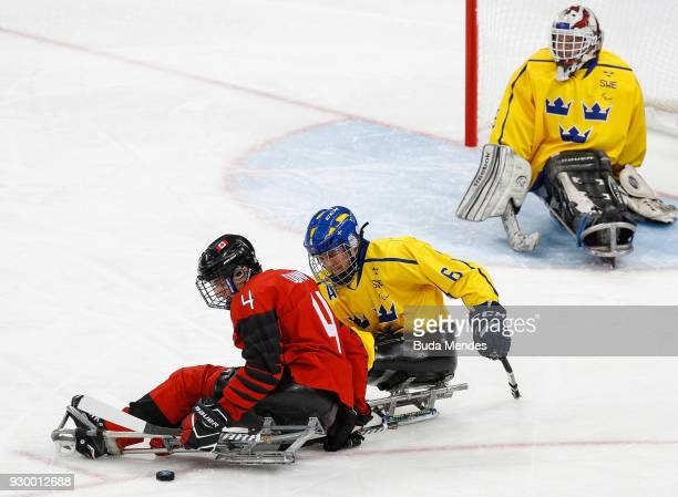 James Dunn of Canada battles for the puck with Peter Nilsson of Sweden in the Ice Hockey Preliminary Round Group A game between Canada and Sweden...
