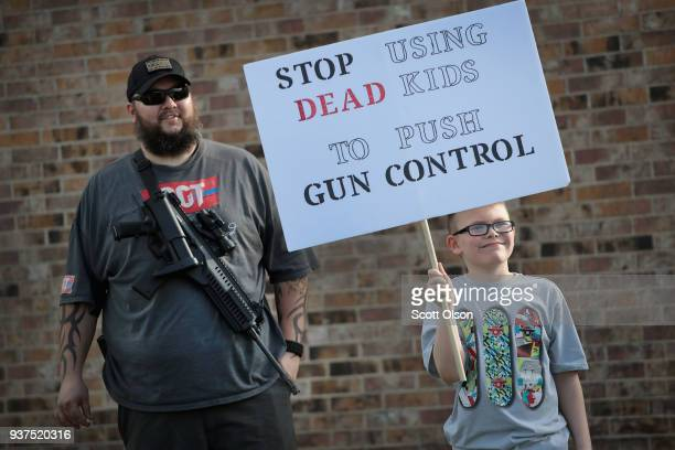 James Everard and his son Steven join a group advocating for the rights of gun owners as they stage a counterprotest near a March for Our Lives rally...