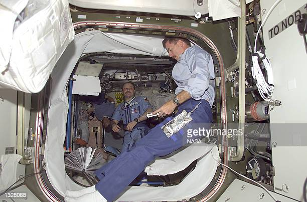 James F Reilly STS104 mission specialist reads over a checklist in the hatchway of the newly installed Quest Airlock July 16 2001 on the...