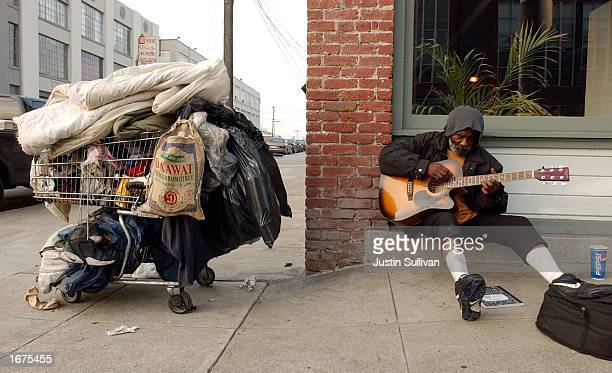 James Faulkner a homeless man plays his guitar while sitting near his shopping cart in the Mission District December 5 2002 in San Francisco...