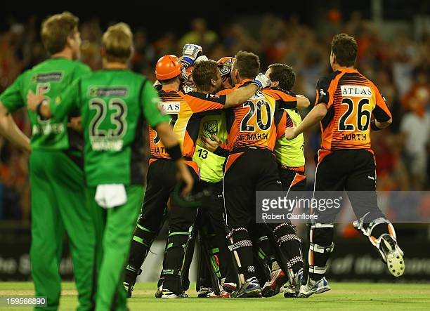 James Faulkner and Shane Warne of the Stars look on as the Scorchers celebrate their win during the Big Bash League semifinal match between the Perth...