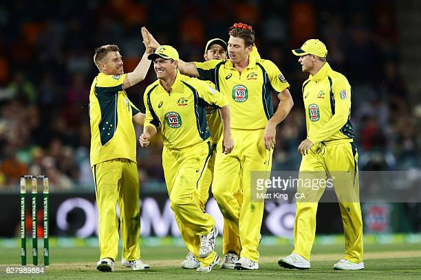 James Faulkner of Australia celebrates with team mates after taking the wicket of Colin Munro of New Zealand during game two of the One Day...
