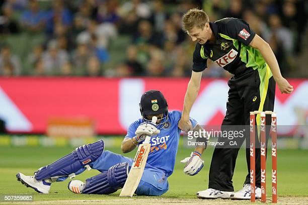 James Faulkner of Australia helps Virat Kohli of India to his feet after he slipped during the International Twenty20 match between Australia and...
