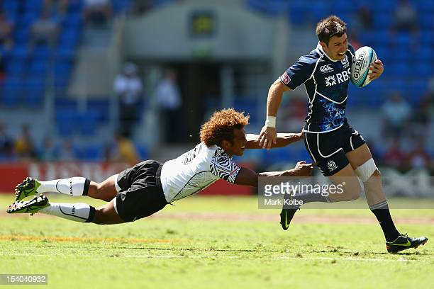 James Fleming of Scotland evades the diving tackle of Osea Kolinisau of Fiji during the match between Scotland and Fiji on day one of the 2012 Gold...