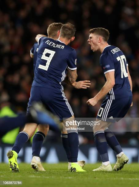 James Forrest of Scotland celebrates with team mates Steven Fletcher and Ryan Christie after scoring his team's first goal during the UEFA Nations...