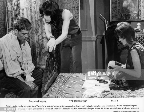 James Fox with his head down as Mick Jagger talks to him in a scene from the film 'Performance' 1970