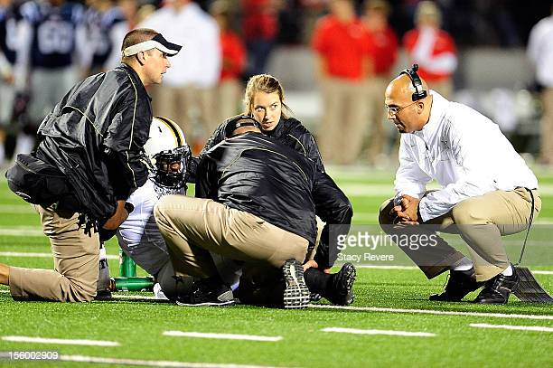 James Franklin head coach of the Vanderbilt Commodores checks on Zac Stacy following an injury in the first quarter during a game against the Ole...