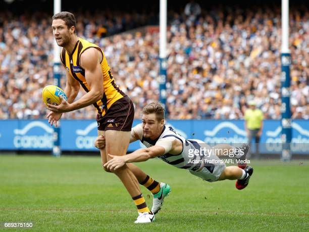 James Frawley of the Hawks is tackled by Tom Ruggles of the Cats during the 2017 AFL round 04 match between the Hawthorn Hawks and the Geelong Cats...