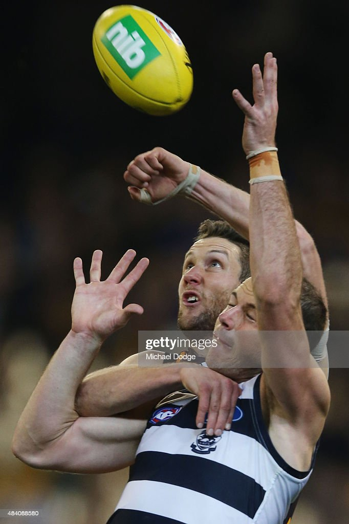 James Frawley of the Hawks punches the ball away from Josh Walker of the Cats during the round 20 AFL match between the Geelong Cats and the Hawthorn Hawks at Melbourne Cricket Ground on August 15, 2015 in Melbourne, Australia.