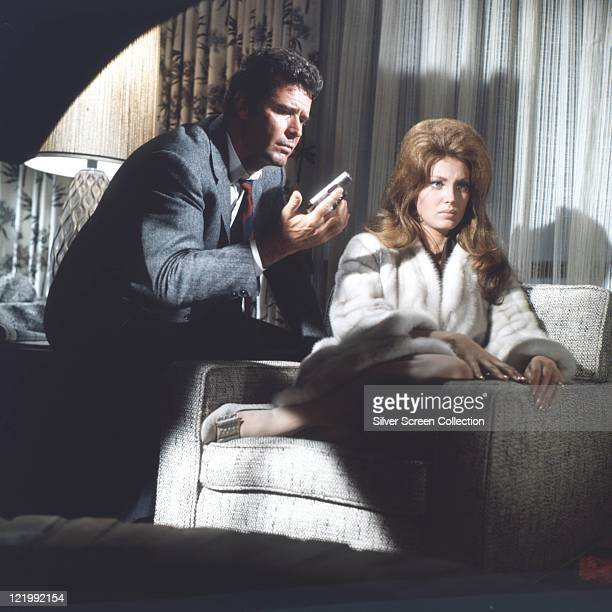 James Garner US actor examining a small handgun as he sits beside an armchair on which sits Gayle Hunnicutt US actress in a publicity still issued...