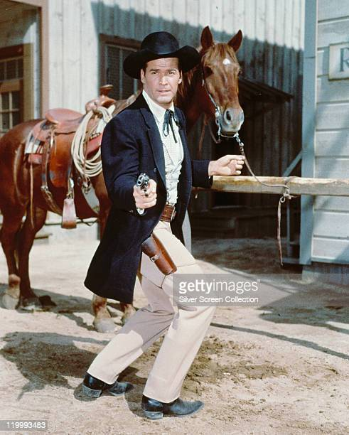 James Garner, US actor, poses in costume, pointing a handgun with a horse behind him, in a publicity portrait issued for the US television show,...