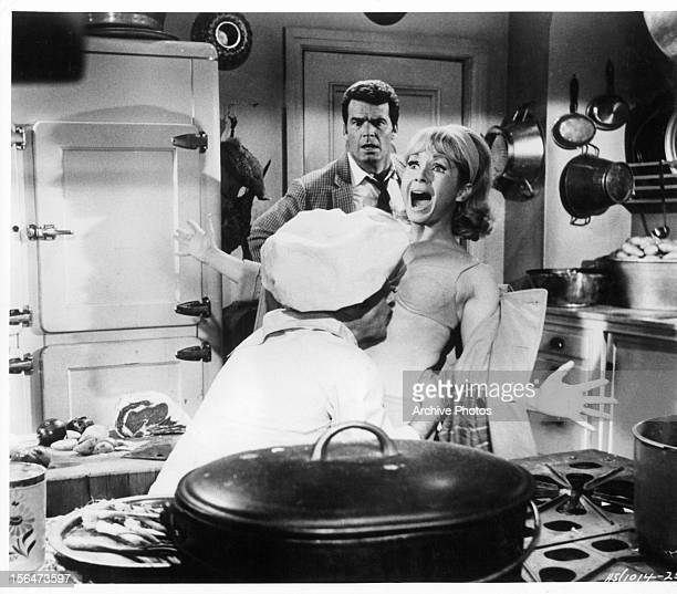James Garner watches from a distance in the kitchen as a chef kisses Debbie Reynold's exposed abdomen in a scene from the film 'How Sweet It Is' 1968