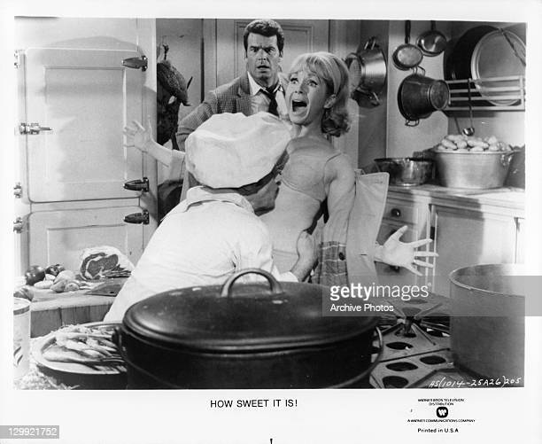 James Garner watches in shock as Debbie Reynolds gets kissed on her chest by the chef in a scene from the film 'How Sweet It Is' 1968