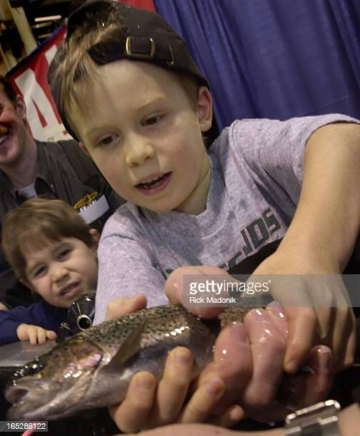 SHOW02 TORONTO ONTARIO James Gay gets a grip on his rainbow trout at the Kidz Trout Pond at the 43rd Annual Toronto International Boat Show held at...
