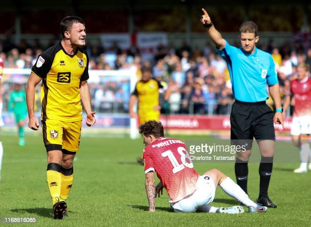 James Gibbons of Port Vale complains as Referee Anthony Backhouse gives a decision for a foul on Danny Whitehead of Salford City during the Sky Bet...