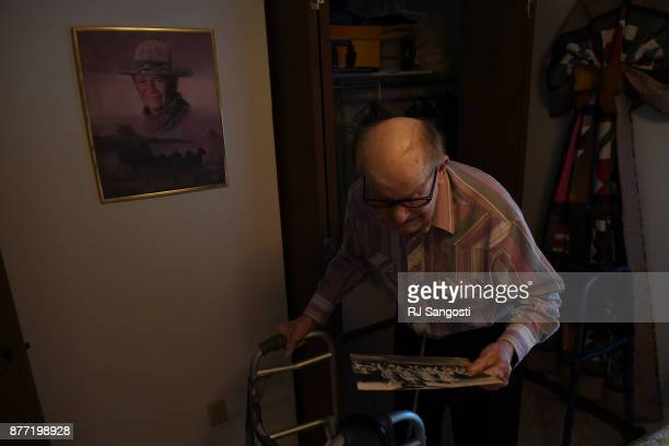 James Gourley digs an old photo of his B17 crew in 1945 from World War II out of a closet at his home on November 13 2017 in Two Buttes Colorado
